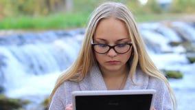 Schönes Mädchen nahe dem Wasserfall mit einer Tablette stock video footage