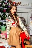 Schönes Mädchen nahe einem Weihnachtsbaum, der auf einem Spielzeugrotwild sitzt Stockbilder