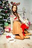 Schönes Mädchen nahe einem Weihnachtsbaum, der auf einem Spielzeugrotwild sitzt Ein lo Lizenzfreie Stockfotos