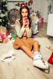 Schönes Mädchen nahe einem Weihnachtsbaum, der mit einer Schale in ihrem h sitzt Stockfotografie