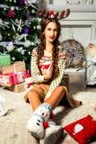 Schönes Mädchen nahe einem Weihnachtsbaum, der mit einer Schale sitzt Stockfotos