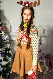 Schönes Mädchen nahe einem Weihnachtsbaum mit einer Schale in ihren Händen Stockfoto