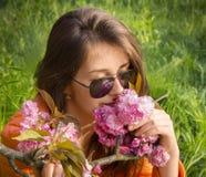Schönes Mädchen riechende eine rosa Kirschblüte-Blumen Stockbilder