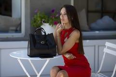 Sch?nes M?dchen s mit einer stilvollen schwarzen Tasche und einem roten Kleid stockbild