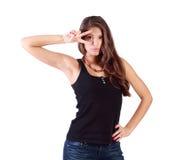 Schönes Mädchen schaut durch Zeichen des Friedens Lizenzfreies Stockfoto