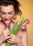 Schönes Mädchen schnüffelt eine Tulpe Stockfotografie