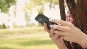 Schönes Mädchen schreibt eine Mitteilung auf dem Smartphone stock video
