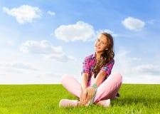 Schönes Mädchen sitzt allein auf Gras und lächelt Stockfotografie
