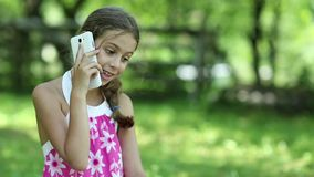 Schönes Mädchen sitzt auf dem Gras und spricht am Telefon stock footage