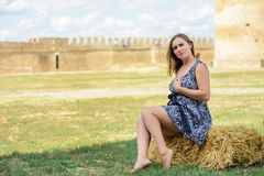 Schönes Mädchen sitzt auf einem Stroh gegen einen Hintergrund einer Festung stockfotografie
