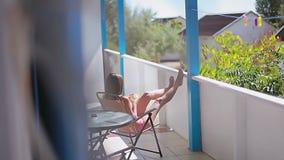 Schönes Mädchen sitzt auf einem Stuhl setzt Füße oben auf die Balustrade und trinkt ein Cocktail stock video
