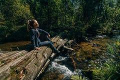 Schönes Mädchen sitzt auf Klotz und dem Kühlen nach Reise Frauenreisender im Sommer gibt Holzbrücke im Hintergrund von weiter lizenzfreie stockfotos