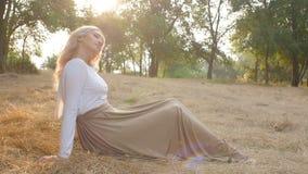 Schönes Mädchen sitzt in einer Wiese, die mit Sonnenlicht in einem Kleid, romantische Stimmung, junge Frau überschwemmt wird, gen stock footage