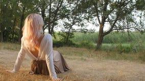 Schönes Mädchen sitzt in einer Wiese, die mit Sonnenlicht in einem Kleid, romantische Stimmung, junge Frau überschwemmt wird, gen stock video footage