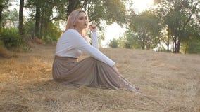 Schönes Mädchen sitzt in einer Wiese, die mit Sonnenlicht in einem Kleid, romantische Stimmung, junge Frau überschwemmt wird, gen stock video