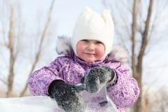 Schönes Mädchen späht heraus von hinten einen Stapel des Eises Stockfoto