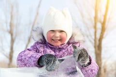 Schönes Mädchen späht heraus von hinten einen Stapel des Eises lizenzfreies stockbild
