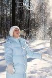 Schönes Mädchen spielt mit Schneeflocken lizenzfreies stockbild