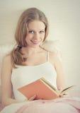 Schönes Mädchen steht im Bett, Lesebuch still Stockbilder