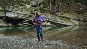 Schönes Mädchen steht, setzend ihre Hände auf die Hüften auf der Bank von einem sauberen Fluss stock video footage