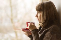 Schönes Mädchen trinkender Tee nahe Fenster Stockfotos
