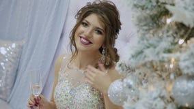 schönes Mädchen trinkt Champagner und sitzt auf dem Sofa im Dekor des neuen Jahres stock video