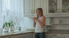 Schönes Mädchen trinkt Tee auf Küche am Morgen stock video