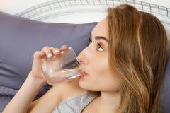 Schönes Mädchen trinkt Wasser morgens im Bettabschluß oben lizenzfreie stockfotografie