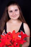 Schönes Mädchen und ein Blumenstrauß der roten Blumen lizenzfreie stockfotos