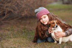 Schönes Mädchen und ihr netter Hund, die im Frühjahr draußen umfasst stockbilder