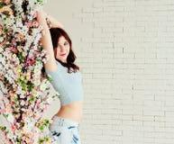 Schönes Mädchen unter den Blumen Stockfotografie