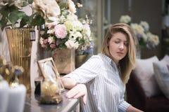 Schönes Mädchen unter den Blumen traurig, das Foto im Rahmen betrachtend Stockfotografie