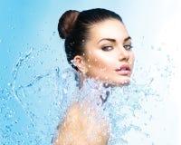 Schönes Mädchen unter Spritzen des Wassers