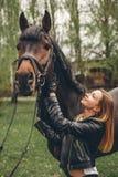 Schönes Mädchen verständigt sich mit einem Pferd im Park lizenzfreies stockfoto