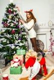 Schönes Mädchen verziert einen Weihnachtsbaum Lizenzfreies Stockbild
