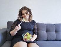 Schönes Mädchen in voller Länge, das auf der Couch mit einer Platte des Salats sitzt stockbild