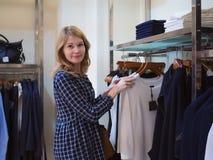 Schönes Mädchen wählt Kleidung in der modischen Butike Frau in einem Cl Lizenzfreie Stockfotos