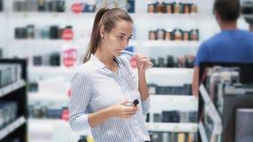 Schönes Mädchen wählt Parfüm in den Kosmetik kaufen, schnüffeln es, Zeitlupe stock video footage