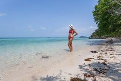 Schönes Mädchen-weißes Haar und rote das swimmingsuit, die auf dem Strand bleibt, entspannend genießen Freiheit Lizenzfreies Stockfoto