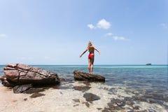 Schönes Mädchen-weißes Haar und rote das swimmingsuit, die auf Felsenstrand, entspannend bleibt und genießen Freiheit Stockfoto