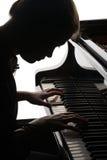 Schönes Mädchen, welches das Klavier spielt Stockfotos