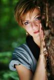 Schönes Mädchen, welches das Lehnen auf einem Baum aufwirft Lizenzfreie Stockbilder