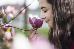Schönes Mädchen, welches die Blumen riecht Blühende Magnolie im Parkgarten Lizenzfreie Stockfotos