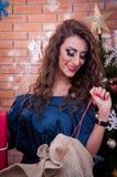 Schönes Mädchen, welches die Geschenke öffnet Stockfotografie