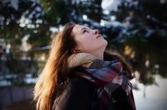 Schönes Mädchen, welches die Himmelstellung im Winterwetter im Wald betrachtet stockfoto