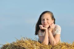 Schönes Mädchen, welches die Natur im Heu genießt lizenzfreies stockbild