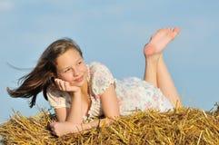 Schönes Mädchen, welches die Natur im Heu genießt stockbild