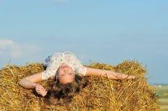 Schönes Mädchen, welches die Natur im Heu genießt Stockbilder