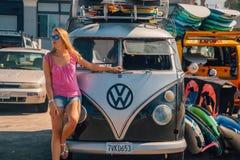 Schönes Mädchen, welches die VW-Hippie bereitsteht stockbild