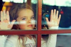 Schönes Mädchen, welches heraus das Fenster schaut lizenzfreie stockbilder